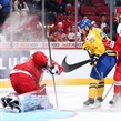 MONTREAL, CANADA - DECEMBER 26: Denmark's Lasse Petersen #30 makes the save while getting a face full of snow from Sweden's Sebastian Ohlsson #25 while Mathias Rondbjerg #7 looks on during preliminary round action at the 2017 IIHF World Junior Championship. (Photo by Andre Ringuette/HHOF-IIHF Images)