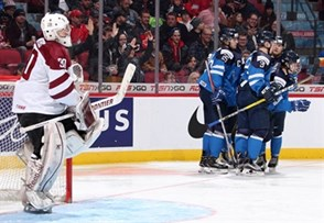 MONTREAL, CANADA - JANUARY 3: Latvia's Mareks Mitens #30 looks on as Finland's Eeli Tolvanen #33 celebrates with teammates after scoring a first period goal during relegation round action at the 2017 IIHF World Junior Championship. (Photo by Andre Ringuette/HHOF-IIHF Images)