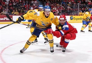 MONTREAL, CANADA - JANUARY 5: Sweden's Gabriel Carlsson #9 and Russia's Kirill Urakov #8 battle for position during bronze medal game action at the 2017 IIHF World Junior Championship. (Photo by Andre Ringuette/HHOF-IIHF Images)